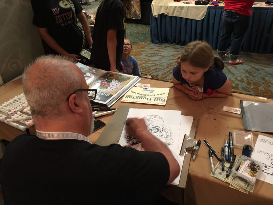 Bill Douglas draws a caricature of Sophia Irmen during the Q-C Planet Comics and Arts convention Sunday.