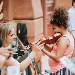 """Carolyn Van De Velde helps a girl try a violin at the June 8 """"Paint the Town"""" event at River Music Experience, Davenport."""